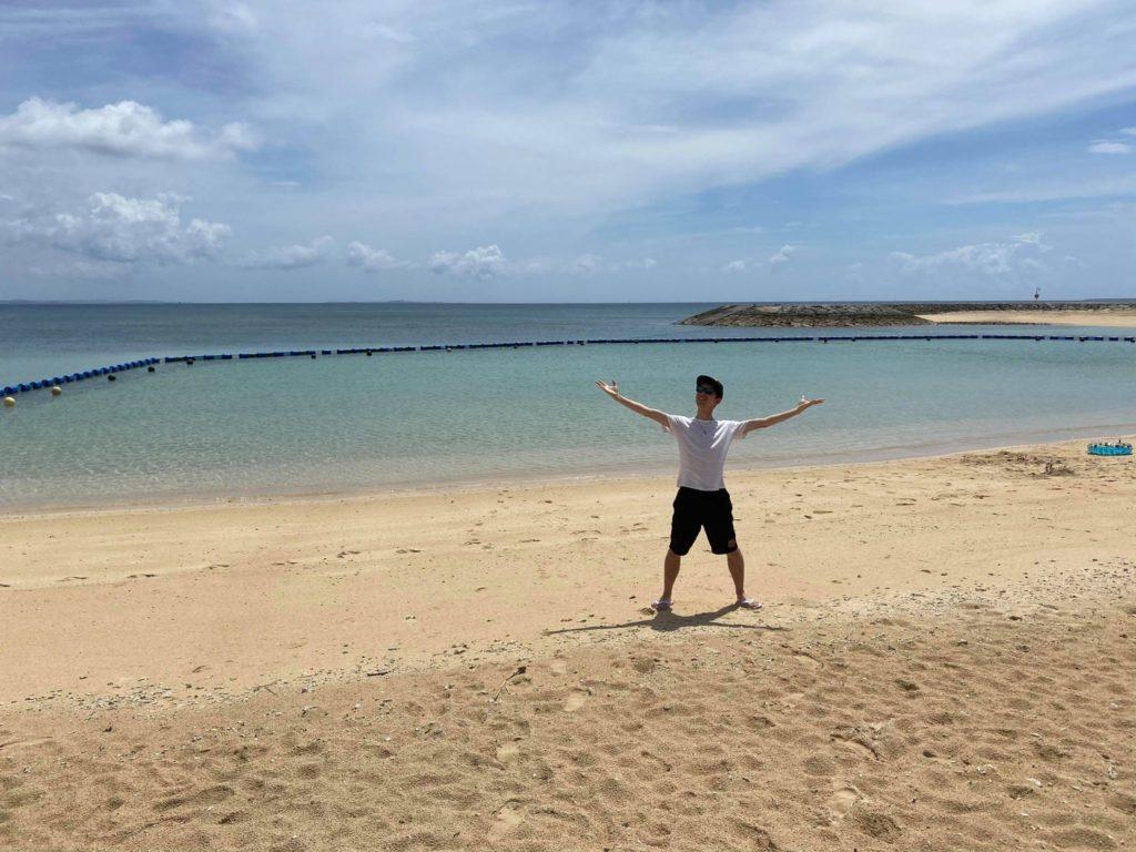 砂浜で両手を広げる青年